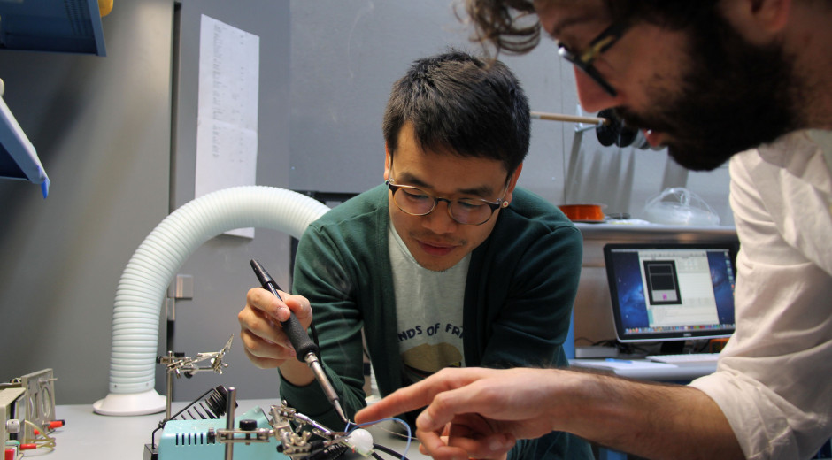 Faculty Casey Anderson assists /lab student Tim Kim with soldering.